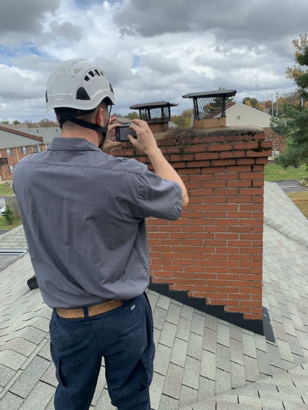 Technician Documenting Damage Of Top Of Chimney By Taking Photos H800